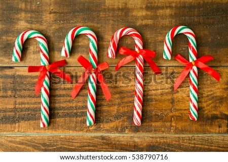 Sweet Candy Canes with red ribbon on a wooden background