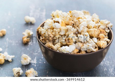 Sweet caramel popcorn in a  bowl on a dark blue background, selective focus - stock photo