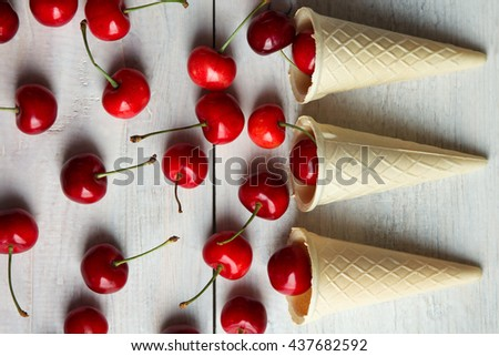 sweet cherries fell out of waffle cone on a wooden background