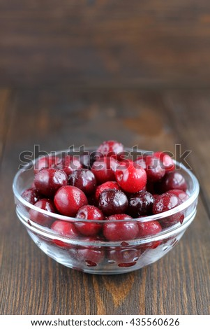 Sweet cherries in glass bowl on wooden table. Juicy ripe cherries for healthy eating. - stock photo