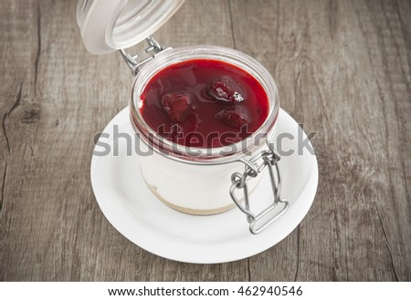 Sweet cherry cheesecake in a mason jar on wooden table