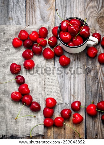 sweet cherry in the cup on wooden table - stock photo