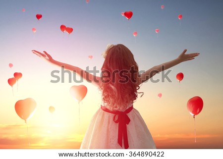 Sweet child girl looking at red balloons. Balloons in shape of heart flying in the sunset sky. Wedding, Valentine, love concept. - stock photo
