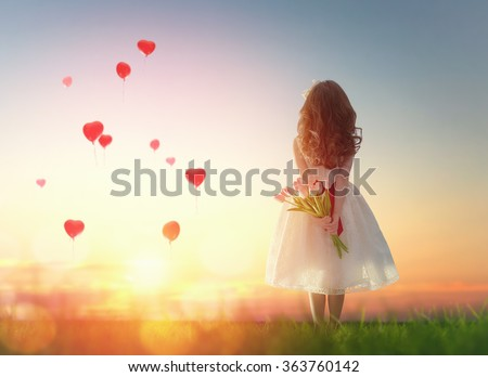 Sweet child girl looking at red balloons. Little child girl holding bouquet of flowers. Balloons in shape of heart flying in the sunset sky. Wedding, Valentine, love concept.  - stock photo
