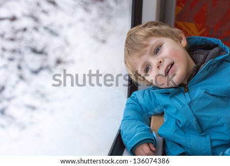 Sweet child looking out train window outside and having fun, while it moving. travel