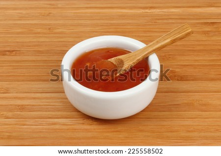 Sweet chilli dipping sauce in a ramekin with a spoon on a bamboo board - stock photo