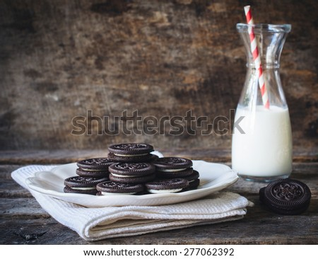 Sweet chocolate cookies and bottle of milk on wooden background,selective focus and blank space - stock photo