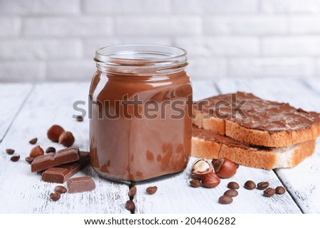 Sweet chocolate cream in jar on table on light background - stock photo