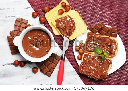 Sweet chocolate hazelnut spread with whole nuts and mint on wooden background - stock photo