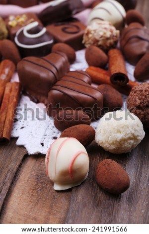 Sweet chocolates assorted on white lace doily on wooden rustic background - stock photo