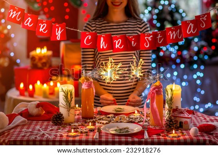 Sweet Christmas decorated table with candles, cookies, drinks and lights on background - stock photo