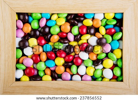 sweet color candy in a wooden frame - stock photo