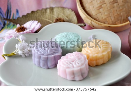 Sweet color of snow skin mooncake on plate with pink background - stock photo