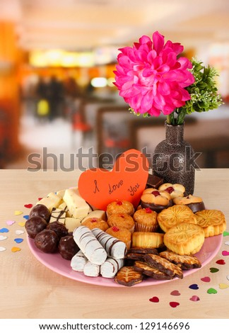 Sweet cookies with valentine card on plate on table in cafe