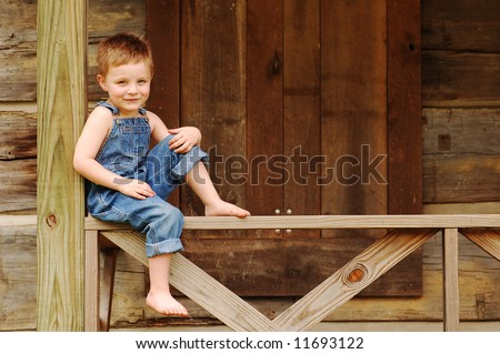Sweet country boy balances on the railing on the porch of a log cabin