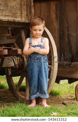 Sweet Country Boy Standing by Wagon Wheel - stock photo