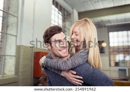 Sweet Couple Concept - Close up handsome Man Carrying his Woman on his Back While Looking Each Other - stock photo