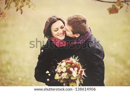 Sweet couple kissing under the tree - stock photo