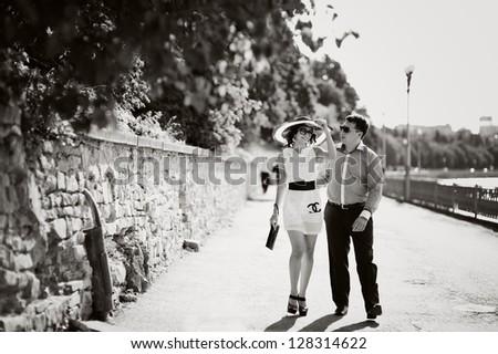 sweet couple walking street, black and white - stock photo