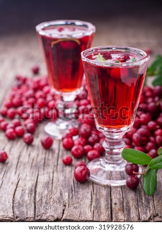 Sweet cranberry liqueur in two glasses on the background of ripe berries on a dark wooden background. selective Focus - stock photo