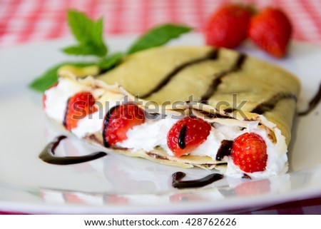 Sweet crepe with chocolate, strawberries, blueberries and some leaves of mind - stock photo