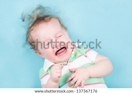 Sweet crying baby on a blue blanket - stock photo
