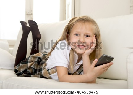 sweet cute and beautiful 6 or 7 years blond old female child in school uniform lying on home sofa couch using internet app on mobile phone playing online game looking happy and relaxed - stock photo