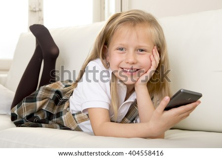 sweet cute and beautiful 6 or 7 years blond old little girl in school uniform lying on home sofa couch using internet app on mobile phone playing online game looking happy and relaxed - stock photo