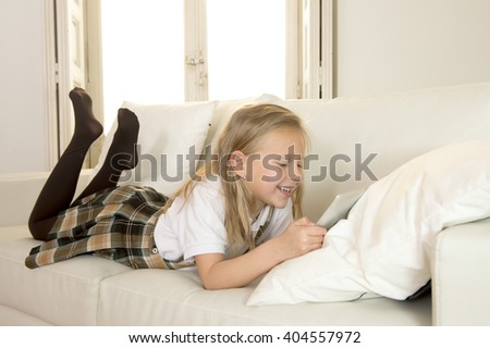 sweet cute and beautiful 6 or 7 years old female child with blond hair in school uniform lying on home sofa couch using internet app on digital tablet pad playing online game smiling happy - stock photo