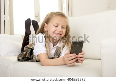 sweet cute and beautiful 6 or 7 years old female child with blond hair in school uniform lying on home sofa couch using internet app on mobile phone playing online game looking happy and relaxed - stock photo