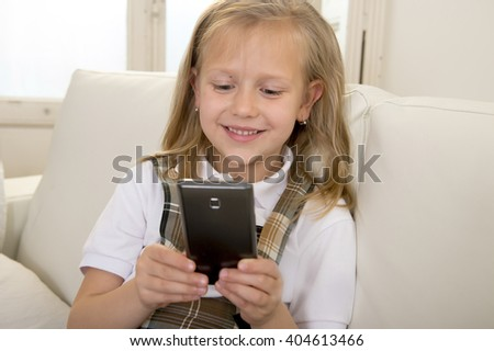 sweet cute and beautiful 6 or 7 years old female child with blond hair in school uniform sitting on home sofa couch using internet app on mobile phone playing online game looking happy and relaxed - stock photo
