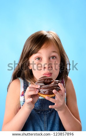 Sweet cute girl eating and enjoying a chocolate glazed donut , on blue background - stock photo