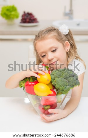 Sweet cute young girl with two ponytails smiles and choose one of healthy ripe colorful vegetables and fruits for cooking. - stock photo