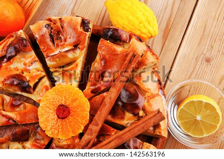 sweet cuts of apple pie on wooden plate served with fresh lemon, mandarin, and cinnamon sticks on table