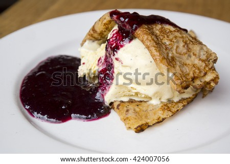 Sweet delicious pancake with ice cream and blueberries jam