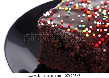 sweet dessert : chocolate cake coated with chocolate on black saucer isolated over white background - stock photo