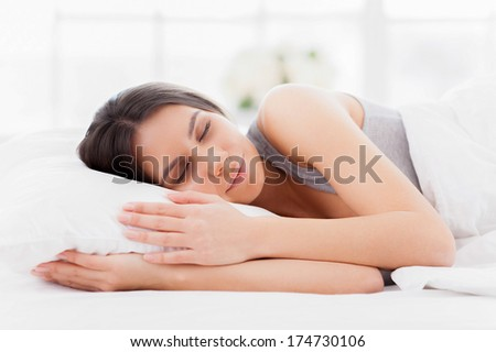 Sweet dreams. Beautiful young woman lying in bed and keeping eyes closed while covered with blanket - stock photo