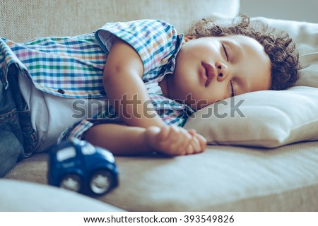 Sweet dreams. Little African baby boy sleeping while lying on couch at home  - stock photo