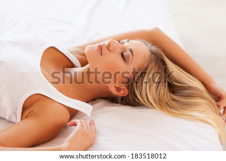 Sweet dreams. Top view of beautiful young woman in singlet lying on bed and keeping eyes closed - stock photo