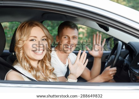 Sweet drive. Portrait of a handsome young man and beautiful blond girlfriend with curvy hair sitting in a white car, smiling happily and waving their hands, view from the window