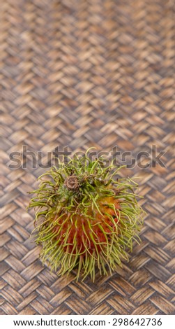 Sweet, exotic and delicious rambutan fruit over wicker background
