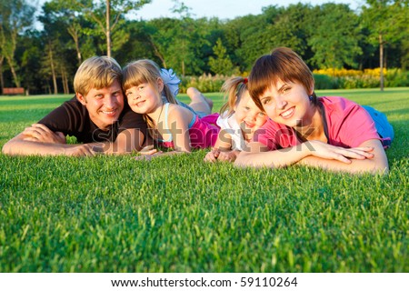Sweet family lying on grass - stock photo