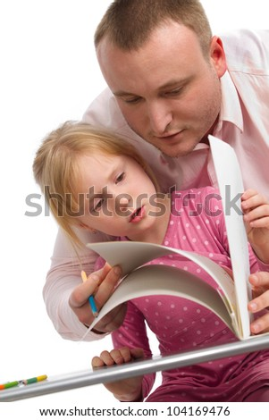 Sweet family reading a book at the table - stock photo