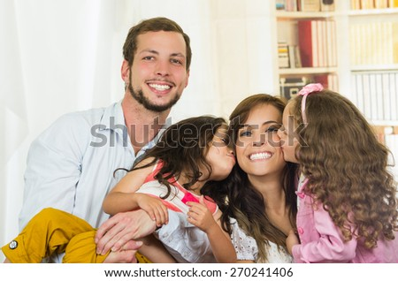 Sweet family with two little girls happily posing - stock photo
