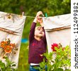 Sweet  five-year girl with clothespin and the clothesline - stock photo