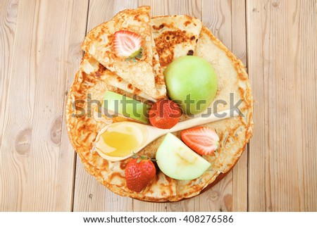 sweet food : big thin pancake with honey strawberries and apple on wooden table - stock photo