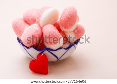Sweet food candy. Pink jellies or marshmallows with sugar in bowl on wooden table decorated with red heart love symbol - stock photo