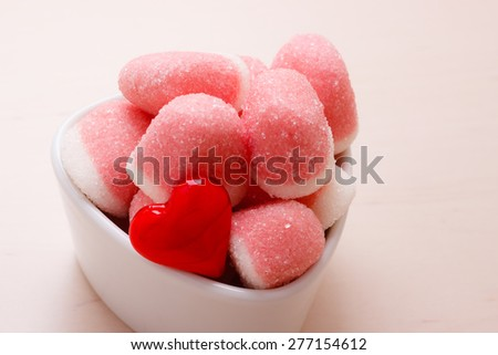 Sweet food candy. Pink jellies or marshmallows with sugar in white bowl on wooden table decorated with red heart love symbol - stock photo