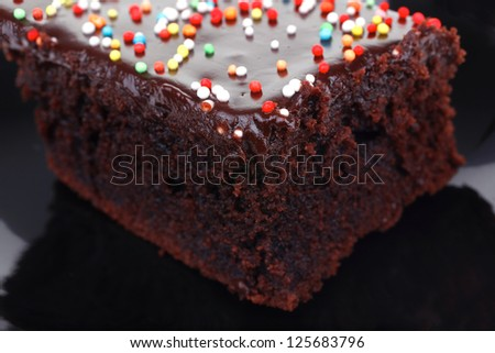 sweet food : chocolate cake coated with chocolate on black saucer isolated over white background - stock photo