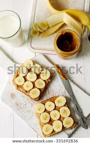 Sweet food. Delicious peanut butter toast with banana - stock photo